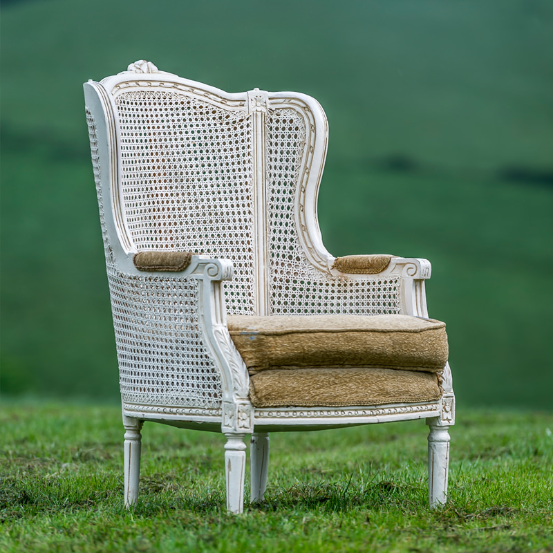 White Wicker Armchair  with worn piping